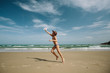 Young Boy throwing paper plane, running on sea beach and enjoy summer day. Blue sky, beautiful beach shore, freedom