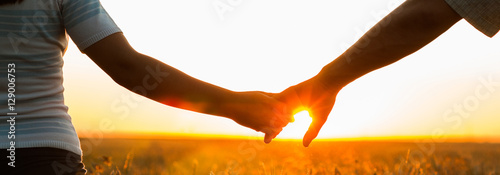 Fotografía  Young couple holding hands in the wheat field on sunny summer day
