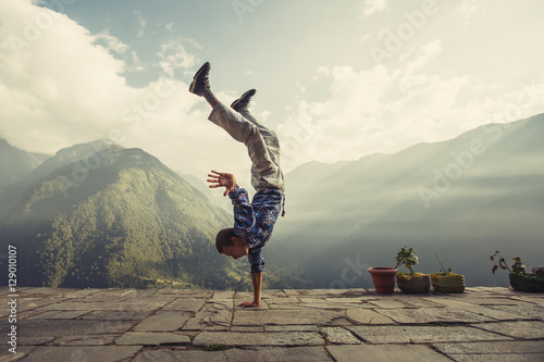 Fotografia  Young sporty man doing handstand exercise in beautiful mountain landscape