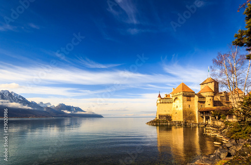 Castle on a lake front with blue sky and mountains Wallpaper Mural