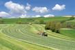 canvas print picture - Zwei Traktoren bei der Ernte von Grünfutter in hügeliger Landschaft
