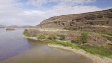 Drone Flight Over Desert River In Canyon With Large Cliff Walls