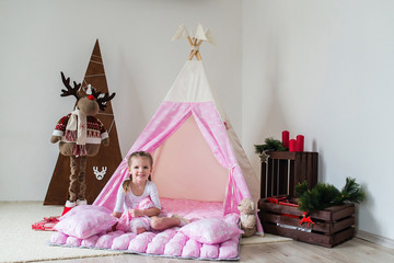 Little girl playing in a tent.