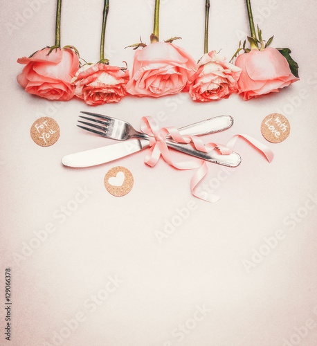 Romantic dinner background with  table place setting : roses border , cutlery and ribbon on pastel background, top view, place for text