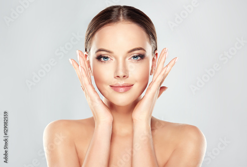 Plakaty do kosmetyczki  beautiful-young-woman-with-clean-fresh-skin-touch-own-face-facial-treatment-cosmetology-beauty-and-spa