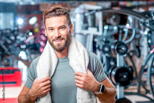 Foto auf Gartenposter Fitness Lifestyle portrait of handsome muscular man standing with towel after the training in the sport gym