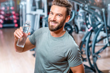 Lifestyle Portrait Of Handsome Muscular Man Drinking Water In The Gym