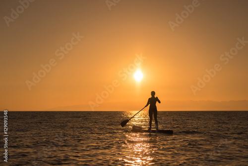 Plakat dziewczyna na pokładzie wiosła w zachód słońca
