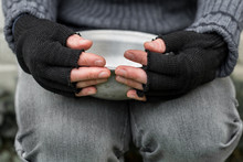Homeless. In The Hands Of One Man Metal Plate. In The Hands Of Black Gloves With The Fingers Cut Off.