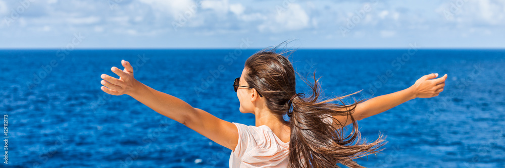 Fototapeta Happy freedom woman with open arms looking at blue sea horizon outdoors. Carefree person living a free life. Panorama horizontal banner crop for success and bliss concept.