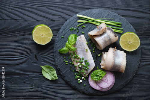 Vászonkép Stone slate tray with herring fillet rolls, black wooden surface