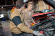 car mechanic point out towards the customer the car problem