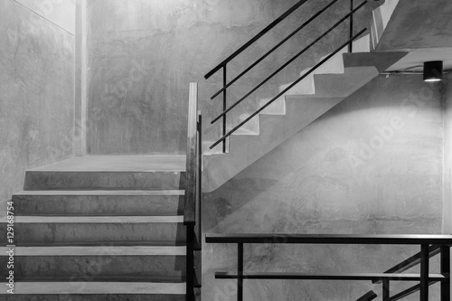 Poster Trappen Empty modern rough concrete stairway with black steel handrail