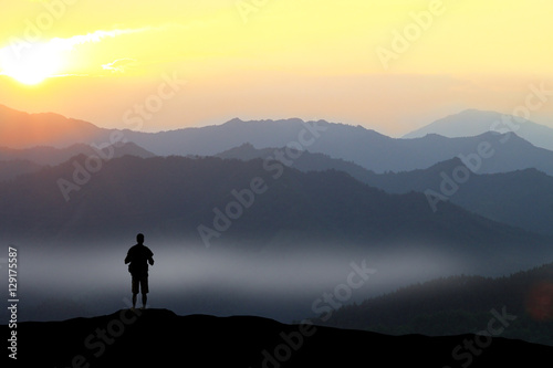 Fotografija Climber standing the top of mountain in sunset background.