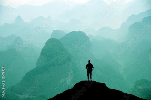 Fotografie, Tablou  Climber standing the top of mountain in sunset background.
