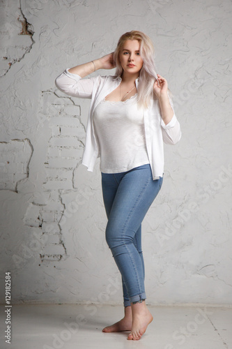 Photo  Portrait of a pretty big blonde in a white shirt on a gray background in full length