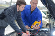 student with instructor repairing a car during apprenticeship