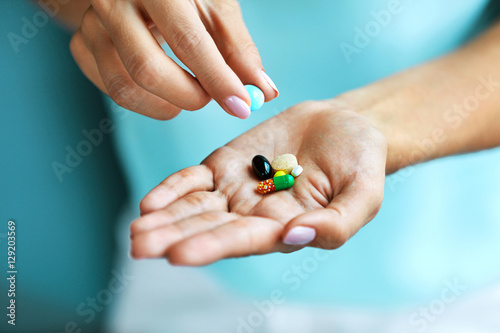 Vitamins And Supplements. Female Hand Holding Colorful Pills