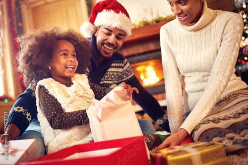 Foto  Happy Afro-American family opening Christmas presents.