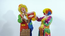 A Couple Of Circus Clowns Playing With Little Box Against White Background