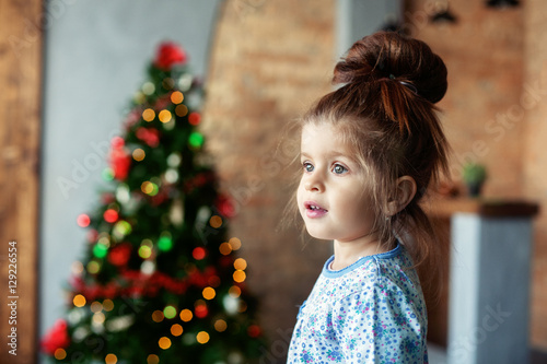 Recess Fitting Roe Little girl in pajamas. The concept of Christmas and New Year.