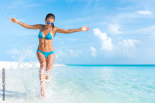 Stampa su Tela Sexy bikini body woman playful on paradise tropical beach having fun playing splashing water in freedom with open arms