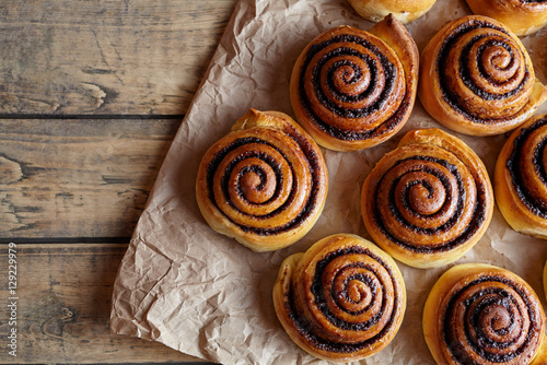 Fotografie, Obraz  Cinnamon rolls buns christmas baking on a wooden breakfast table and parchment paper
