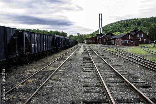 Railroad tracks running through old railroad yard next to rusting coal hoppers and maintenance shops
