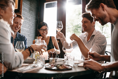 Young man with friends at restaurant - 129235543