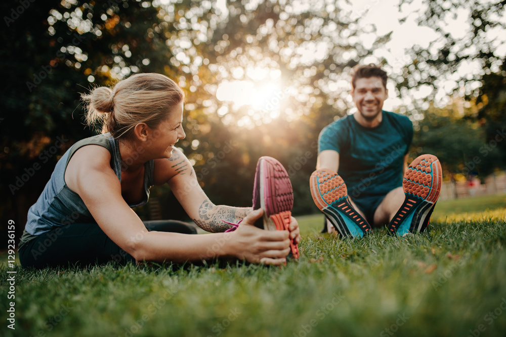 Fototapety, obrazy: Young couple doing their stretches in the park