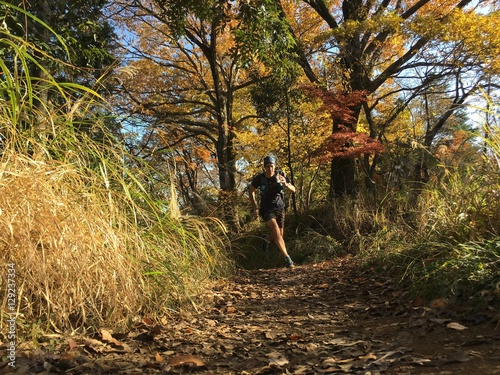 Fotografía  Autumn leaves and man running on country trail