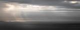 un phare au large sous un rayon de soleil à travers un ciel orageux gris en format panoramique