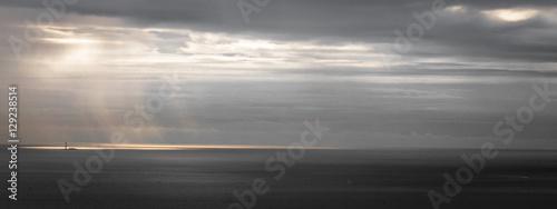 latarnia morska na morzu pod promieniem słońca przez burzliwe szare niebo w panoramicznym formacie