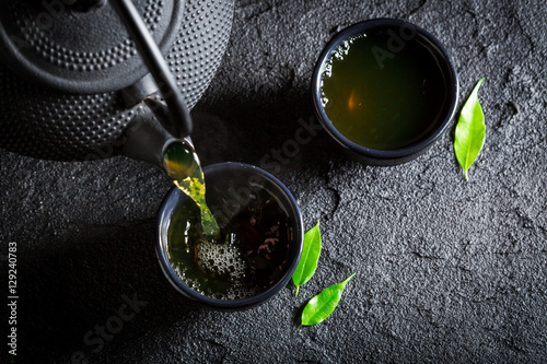Plakat Wyśmienicie zielona herbata z teapot i filiżanką na czerni kołysa