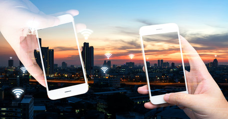 Internet of things , iot , smart home , smart city and network connect concept. Hands holding white phones and wifi icon with city sunset view.
