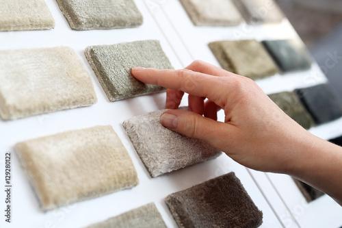 Fototapeta Sklep z dywanami. Kobieta w sklepie z dywanami wybiera dywan z próbnika obraz