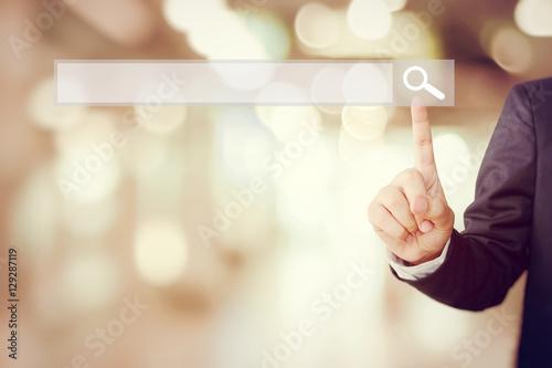Fotografia  Businessman hand touching blank search bar over blur background