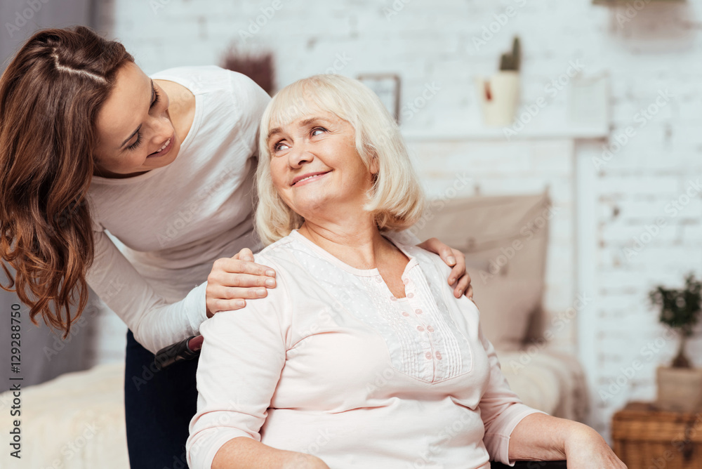 Fototapeta Cheerful woman taking care of her grandmother in wheelchair