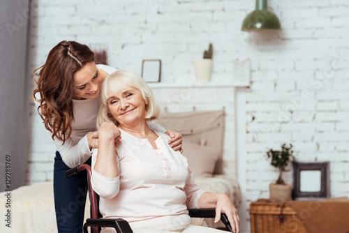Fotografia  Rozochocona starsza kobieta sittig w wózku inwalidzkim