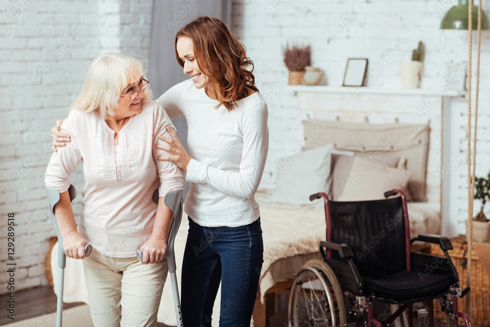 Fototapeta Pleasant caring woman helping with rehabilitation her disabled grandmother