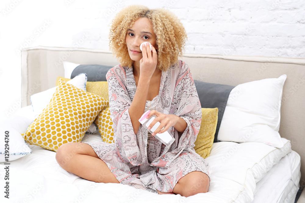 Fototapeta Poranna pielęgnacja skóry twarzy. Kobieta przemywa twarz siedząc na łóżku w sypialni