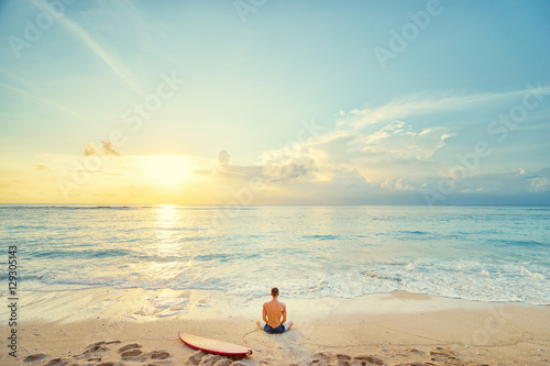 Surfing and meditation. Enjoying sunset.. Relaxed young man sitting on lotus position with surf board on the beach.