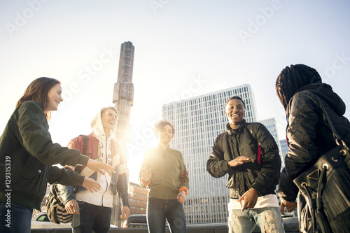 Low angle view of happy teenagers dancing in city against clear sky