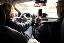 Senior Woman Driving Car While Sitting By Man Taking Selfie Through Smart Phone