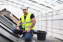 Portrait Of Manual Worker Sitting With Tools On Metal At Construction Site