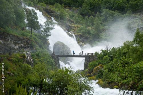 Foto auf Leinwand Skandinavien Tourists on the bridge and waterfall splashes shower