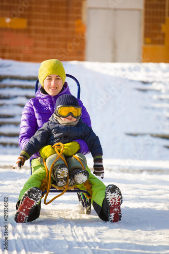 A mom with a child sledding.