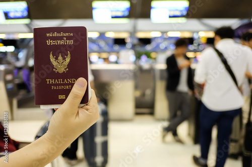 Hand holding Thai passport in front of check-in counter at the a