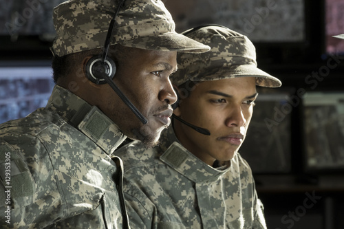 Photo  Two military drone operators  in front of a computer, profile shot