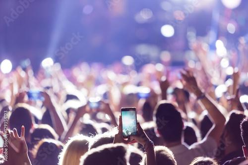 Fotografie, Obraz  Hand with a smartphone records live music festiva
